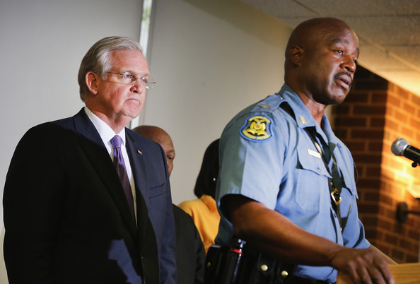 Missouri Governor Jay Nixon (L) listens as Capt. Ronald Johnson of the Missouri Highway Patrol, the man he appointed to take control of security operations in the city of Ferguson, addresses the press on August 14, 2014 in St. Louis, Missouri.