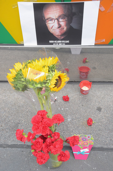 Flowers, tootsie rolls, a card, and a candle are placed in memory of Robin Williams in front of Carolines on Broadway comedy club on August 12, 2014 in New York City.