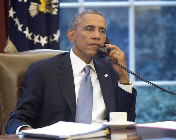 President Barack Obama, seen through an Oval Office window, speaks on the phone with King Abdallah Abd al Aziz of the Kingdom of Saudi Arabia at the White House on September 10, 2014 in Washington, DC.