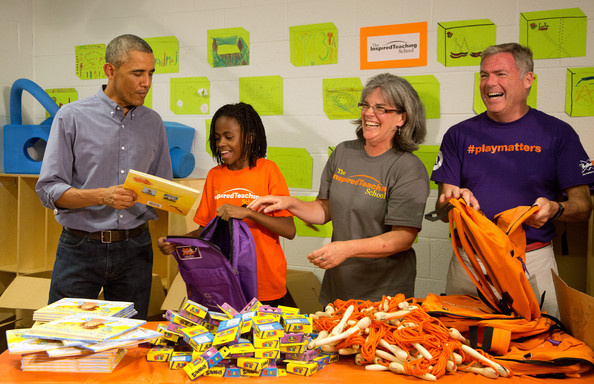 President Barack Obama and volunteers take part in a service project filling backpacks with books and toys for homeless children at the Inspired Teaching School to mark the September 11th National Day of Service and Remembrance on September 11, 2014 in Washington, DC.