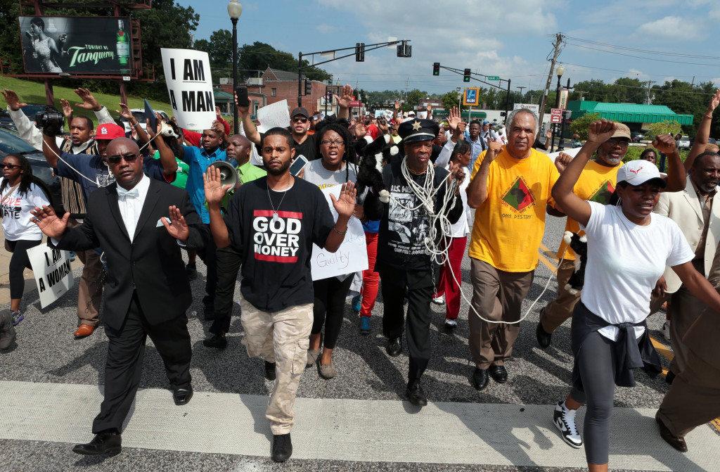 Marchers move south on S. Florissant Road in downtown Ferguson, Mo., on Monday, Aug. 11, 2014 as they demonstrate at police headquarters against the police shooting of Michael Brown.