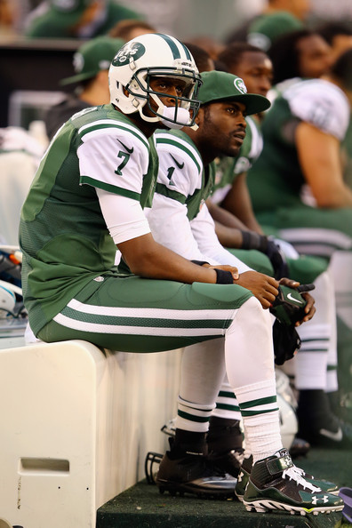 Quarterbacks Geno Smith #7 of the New York Jets and Michael Vick #1 look on from the bench in the fourth quarter against the Buffalo Bills at MetLife Stadium on October 26, 2014 in East Rutherford, New Jersey. The Bills won 43-23