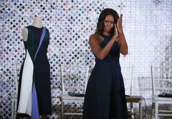 U.S. first lady Michelle Obama applauds during a session of a Fashion Education Workshop in the East Room of the White House October 8, 2014 in Washington, DC.