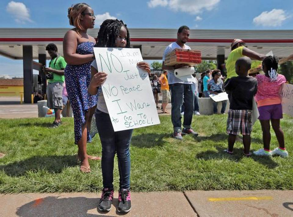 Ariel Elliott, 6, of Ferguson, Mo., protests for her first time on Thursday, Aug. 14, 2014, in front of the burned out QuikTrip in Ferguson.