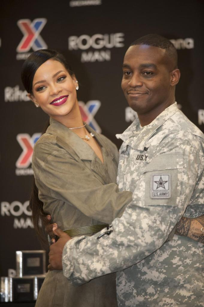 Rihanna is hugged by CW2 William Fearrington during an event promoting her Rogue Man cologne at Ft. Belvoir Exchange on Wednesday, Nov. 12, 2014 in Ft. Belvoir, Va.
