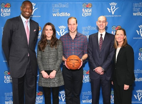 Prince William, Duke of Cambridge (C) and Catherine, Duchess of Cambridge (2nd L) pose with NBA Commissioner Adam Silver (2nd R), Global Ambassador Dikembe Mutombo (L) and Sr. Vice President, Community & Player Programs Kathleen Behrens (R) as they attend the Cleveland Cavaliers vs. Brooklyn Nets game at Barclays Center on December 8, 2014 in the Brooklyn borough of New York City.