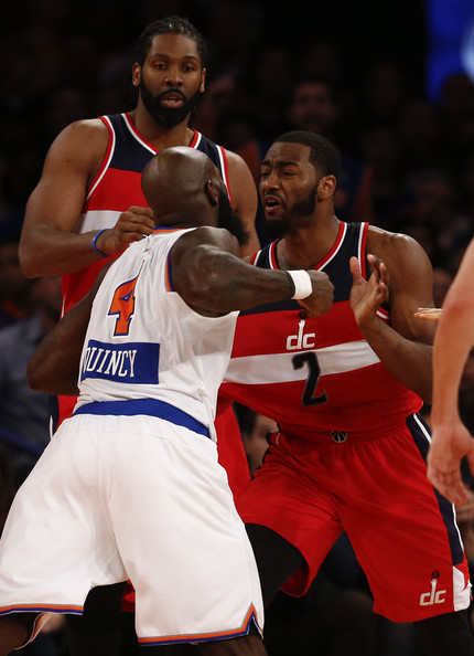 Quincy Acy #4 of the New York Knicks scuffle with John Wall #2 of the Washington Wizards in the second half of their game at Madison Square Garden on December 25, 2014 in New York City.