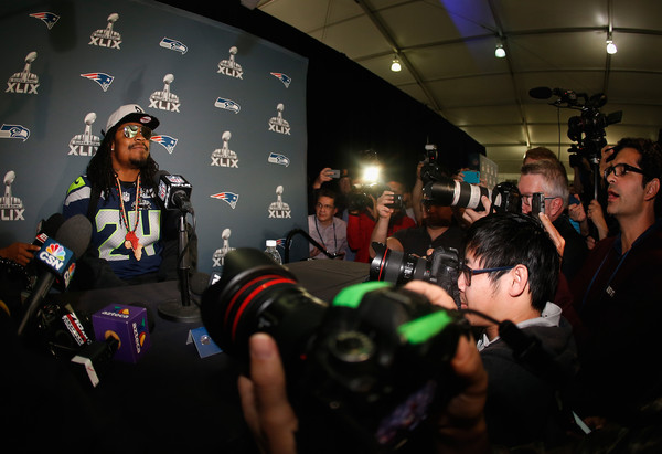 Running back Marshawn Lynch #24 of the Seattle Seahawks sits at his podium during a Super Bowl XLIX media availability at the Arizona Grand Hotel on January 28, 2015 in Chandler, Arizona