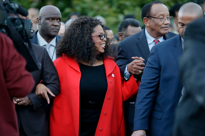 """Oprah Winfrey locks arms with some of the cast of the new movie """"Selma"""" as they march to the Edmund Pettus Bridge in honor of Martin Luther King Jr., Sunday, Jan. 18, 2015, in Selma, Ala."""