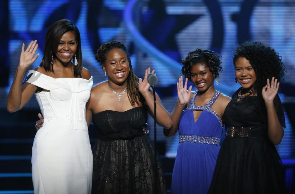 First Lady Michelle Obama, left, waves while standing on stage with Making A Difference award winners, from left, Kaya Thomas, Chental-Song Bembry and Gabrielle Jordan during a taping of the Black Girls Rock award ceremony at the New Jersey Performing Arts Center, Saturday, March 28, 2015, in Newark
