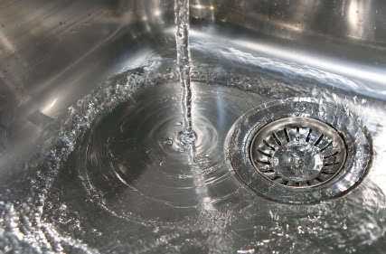 Stainless steel kitchen sink with running water going down the drain
