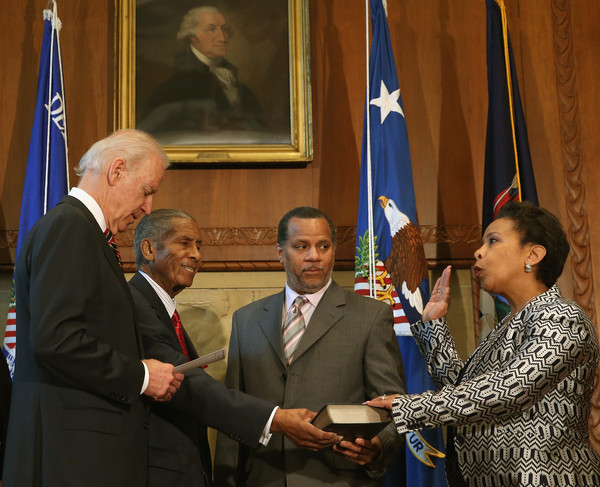 Vice President Joe Biden (L) swears in Loretta Lynch (R) as Attorney General as her husband Stephen Hargrove (2R) and father Lorenzo Lynch (2L) stand nearby during an event at the Justice Department April 27, 2015 in Washington, DC.