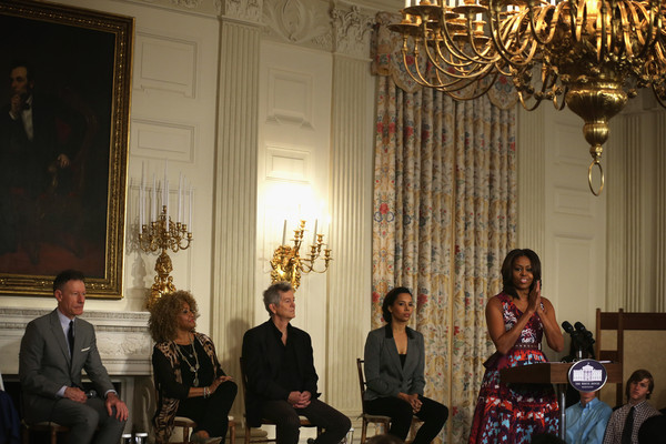 "U.S. first lady Michelle Obama (R) speaks as musicians Lyle Lovett (L), Darlene Love (2nd L), Rodney Crowell (3rd L), and Rhiannon Giddens (4th L) listen during a workshop for students on ""The History of Gospel Music"" April 14, 2015 at the State Dining Room of the White House in Washington, DC."
