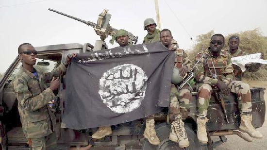 Nigerian soldiers hold up a Boko Haram flag