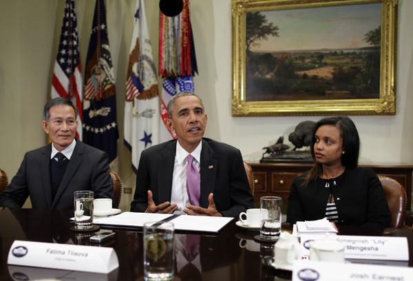 """President Barack Obama (2nd L) speaks as Nguyen Van Hai (L), better known by his pen name Dieu Cay, of Vietnam, and Simegnish """"Lily"""" Mengesha (R) of Ethiopia listen during a roundtable with persecuted journalists at the Roosevelt Room of the White House May 1, 2015 in Washington, DC."""