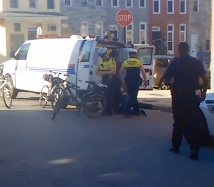 A cell phone video shot April 12 at Baker and Mount streets shows officers putting Freddie Gray in leg shackles and flexi-cuffs before putting him back in the van, head first and on his stomach. (Baltimore Sun)