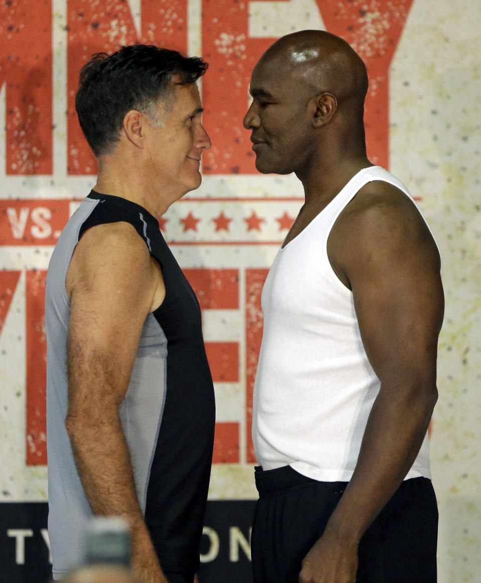 In this Thursday, May 14, 2015, photo, former Republican presidential candidate Mitt Romney, left, and five-time heavyweight boxing champion Evander Holyfield face each other during an official weigh-in, in Holladay, Utah.