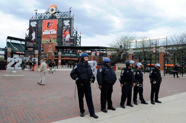 Police stand watch outside Oriole Park at Camden Yards before the game was postponed between the Baltimore Orioles and the Chicago White Sox on April 27, 2015 in Baltimore
