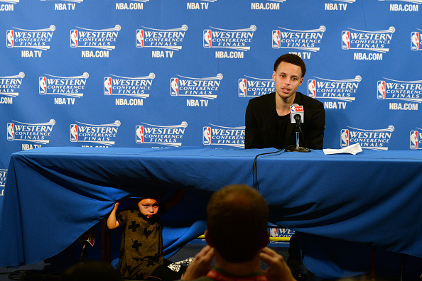 Stephen Curry #30 of the Golden State Warriors and his daughter Riley talking with the media at a press conference after the game against the Houston Rockets during Game One of the Western Conference Finals during the NBA Playoffs on May 19, 2015 at ORACLE Arena in Oakland, California.