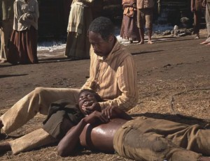 Fiddler (Louis Gossett Jr.) holds Kunta Kinte (LeVar Burton) after he is whipped into accepting his new name, Toby