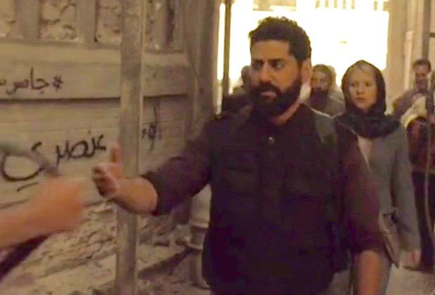 "Scene from ""Homeland"" showing the words ""Homeland is Racist"" written in Arabic as graffiti"