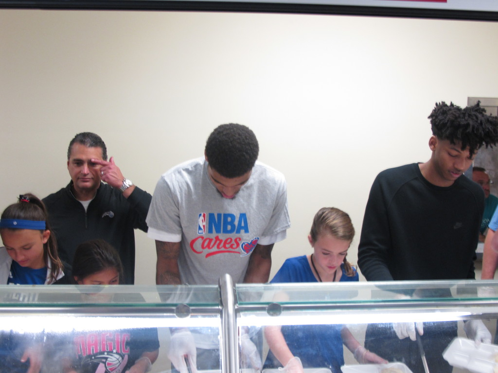 Magic players Devyn Marble and Elfrid Payton serve food at the Magic's Coalition for the Homeless Thanksgiving breakfast. Photo Credit: Gary Bassing, Orlando Magic.