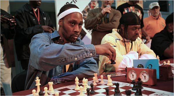 RZA playing a round of chess with some of the local youth.