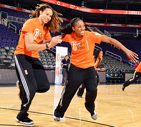 Brittney Griner #42 of the Phoenix Mercury and Glory Johnson #25 of the Tulsa Shock run during a WNBA All-Star Cares event on July 18, 2014