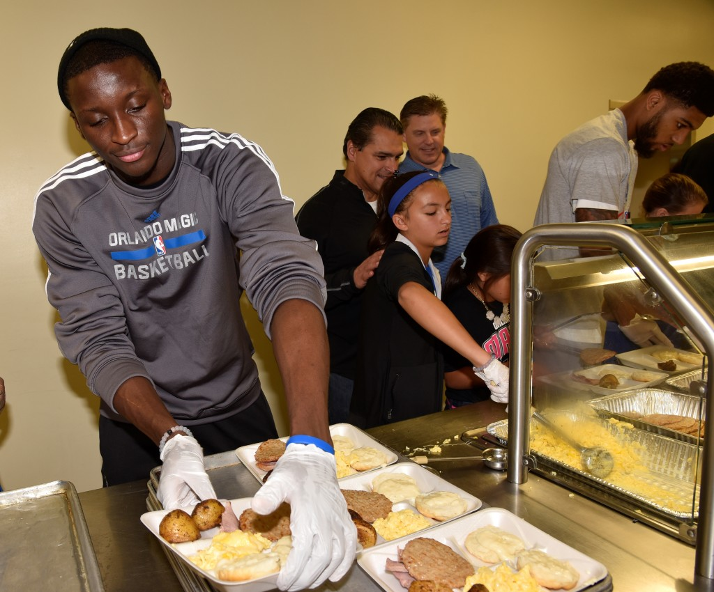 Magic guard Victor Oladipo prepares food to serve to the residents at the Coalition for the Homeless. Photo Credit Gary Bassing, Orlando Magic.
