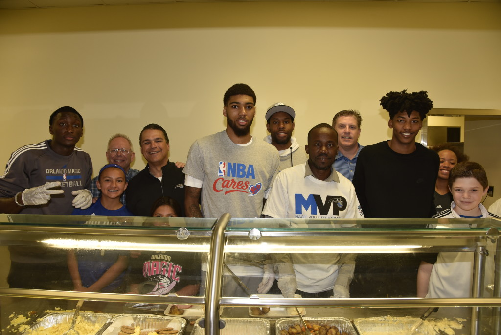 Pictured: Magic CEO Alex Martins, Magic players Victor Oladipo, Elfrid Payton, Devyn Marble, CJ Watson, Magic COO Charlie Freeman, Coalition for the Homeless President/CEO Brent Trotter and Magic staff and families help serve food to the Coalition for the Homeless residents. Photo Credit: Gary Bassing, Orlando Magic
