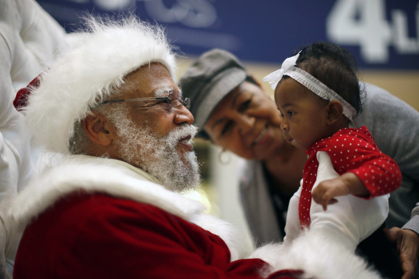 African American Santa Claus Langston Patterson (L), 77, greets four-month-old Raelyn Price as her grandmother Gloria Boissiere looks on, at Baldwin Hills Crenshaw Plaza mall in Los Angeles, California, December 16, 2013. Patterson has worked as Santa since 2004 at the mall, which is one of the few in the country with a black Santa Claus. A New Mexico teacher who told an African American student that Santa Claus was white has been put on paid administrative leave, an official said on Monday. REUTERS/Lucy Nicholson (UNITED STATES - Tags: SOCIETY)