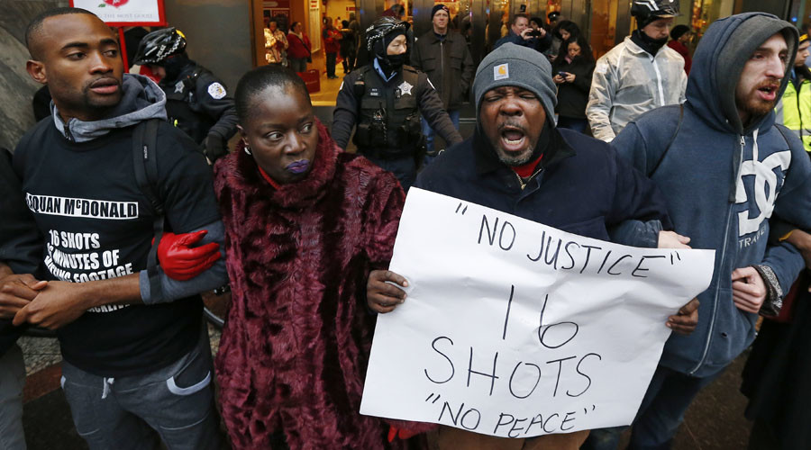 Demonstators link arms in solidarity as they protest last year's shooting death of black teenager Laquan McDonald by a white policeman and the city's handling of the case in Chicago