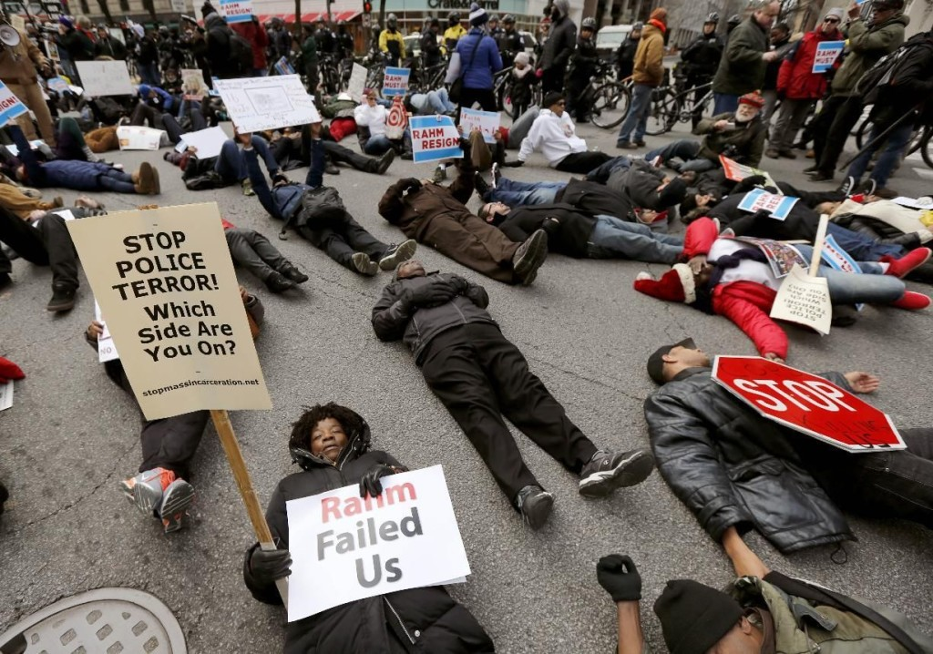 Protesters block an intersection on Chicago's Magnificent Mile, calling for the resignation of Mayor Rahm Emanuel, Thursday, Dec. 24, 2015, in Chicago.