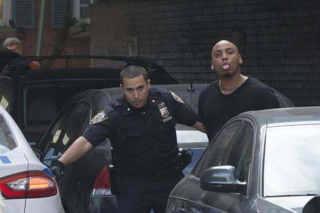 Smith is escorted by a police officer after being charged with criminal trespass following an incident in an NYC club.