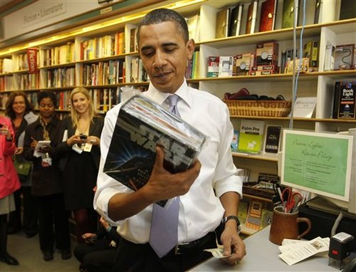 President Barack Obama buys a Star Wars pop up book for Press Secretary Robert Gibbs's son Ethan during unannounced stop at Prairie Lights book shop in Iowa City, Iowa, Thursday, March 25, 2010.
