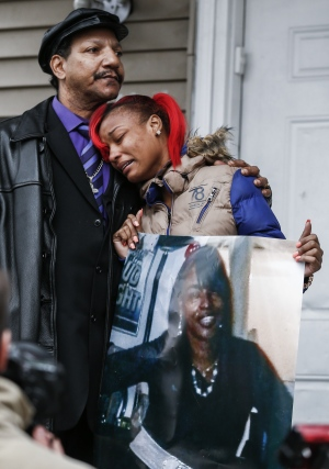 LaTonya Jones, right, is comforted by her father Garry Mullen as she holds a picture of her mother Bettie Jones during a vigil outside of the home where Jones was shot alongside neighbor Quintonio LeGrier