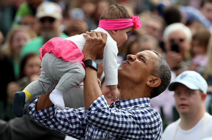 WASHINGTON, DC - MARCH 28: U.S. President Barack Obama lifts Stella Munoz into the air while greeting guests on the South Lawn of the White House during the annual White House Easter Egg Roll March 28, 2016 in Washington, DC. Thousands of people attended the 138-year-old tradition of rolling colored eggs down the White House lawn that was started by President Rutherford B. Hayes in 1878. (Photo by Win McNamee/Getty Images)