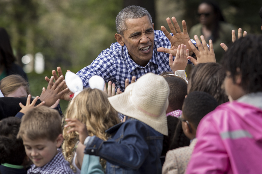 "WASHINGTON, DC - MARCH 28: President Barack Obama gives high fives to children after reading from the book ""Where the Wild Things Are"" during the annual White House Easter Egg Roll on the South Lawn of the White House March 28, 2016 in Washington, DC. The tradition dates back to 1878 when President Rutherford B. Hayes allowed children to roll eggs on the South Lawn. (Photo by Drew Angerer/Getty Images)"