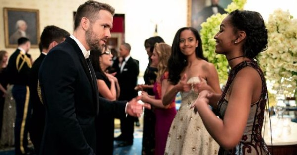 Actor Ryan Reynolds chats with Sasha Obama, while big sis Malia gives a two thumbs up!