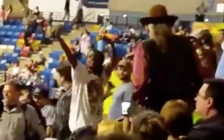 Rakeem Jones (hands raised) moments before he is sucker-punched by man in hat at Donald Trump rally (March 9, 2016)