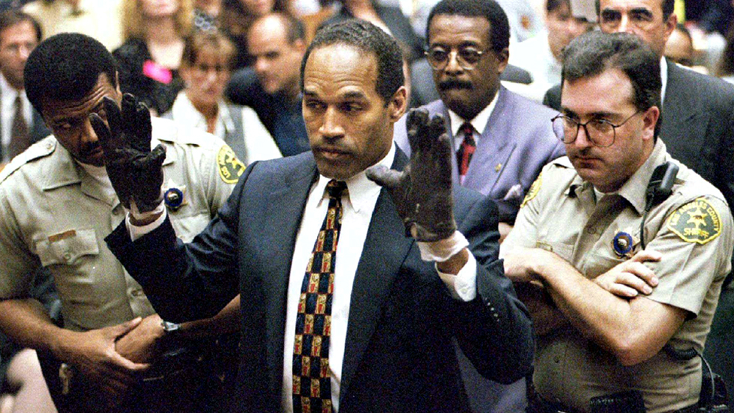 O.J. Simpson holds up his hands to the jury wearing the infamous gloves found at the crime scene and his home in this June 15, 1995 file photo.