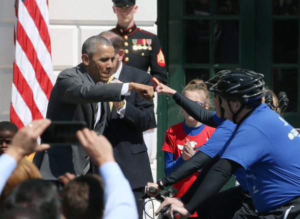 U.S. President Barack Obama fist pumps a rider after signaling the start of the Wounded Warrior Ride, on the South Lawn of the White House, April 14, 2016 in Washington, DC.