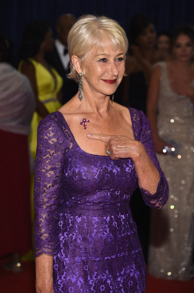 Dame Helen Mirren indicates a symbol honoring the late musician Prince on her shoulder as she attemds the the 102nd White House Correspondents' Association Dinner on April 30, 2016 in Washington, DC.