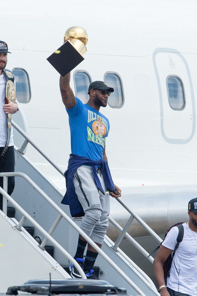 LeBron James #23 of the Cleveland Cavaliers hoists the trophy as he gets off the plane as the team returns to Cleveland after wining the NBA Championships on June 20, 2016 in Cleveland, Ohio.