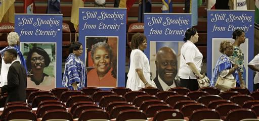 People walk past photos of some of the victims of last year's shooting at Mother Emanuel AME Church before a memorial service honoring those killed in Charleston, S.C., Friday, June 17, 2016. (AP Photo/Chuck Burton)
