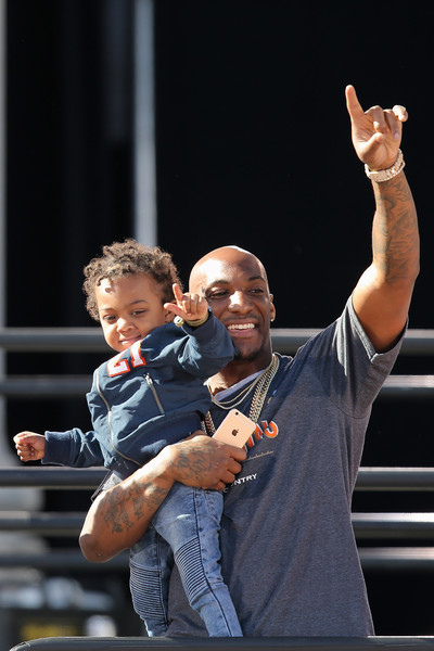 Aqib Talib of the Denver Broncos waves to the fans with one of his children as the Super Bowl 50 Champion Denver Broncos are honored at a rally on the steps of the Denver City and County Building on February 9, 2016 in Denver, Colorado