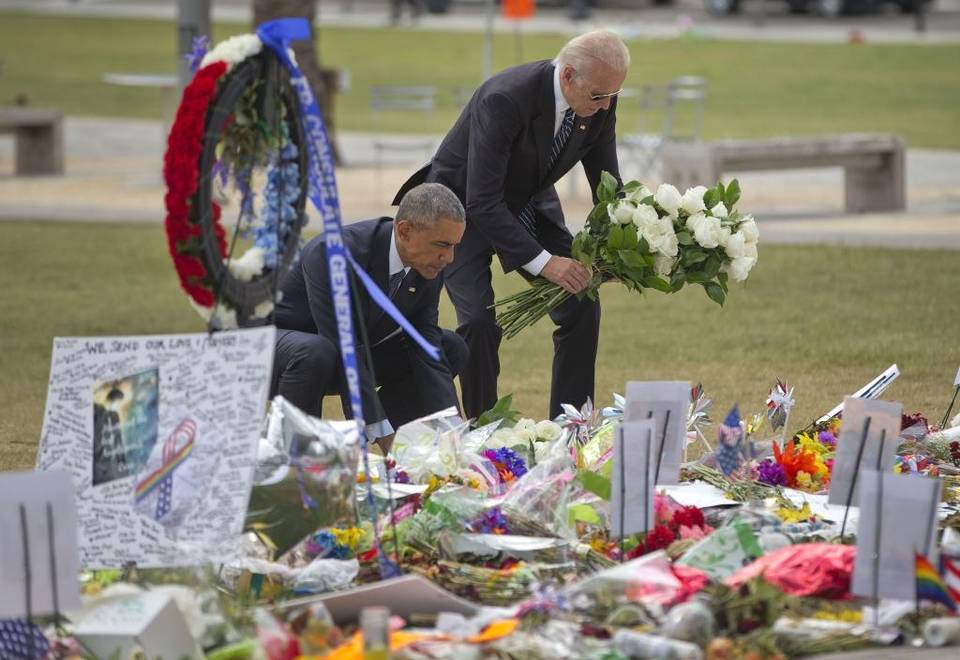 President Barack Obama and Vice President Joe Biden place flowers down during their visit to a memorial to the victims of the Pulse nightclub shooting, Thursday, June 16, 2016 in Orlando, Fla.
