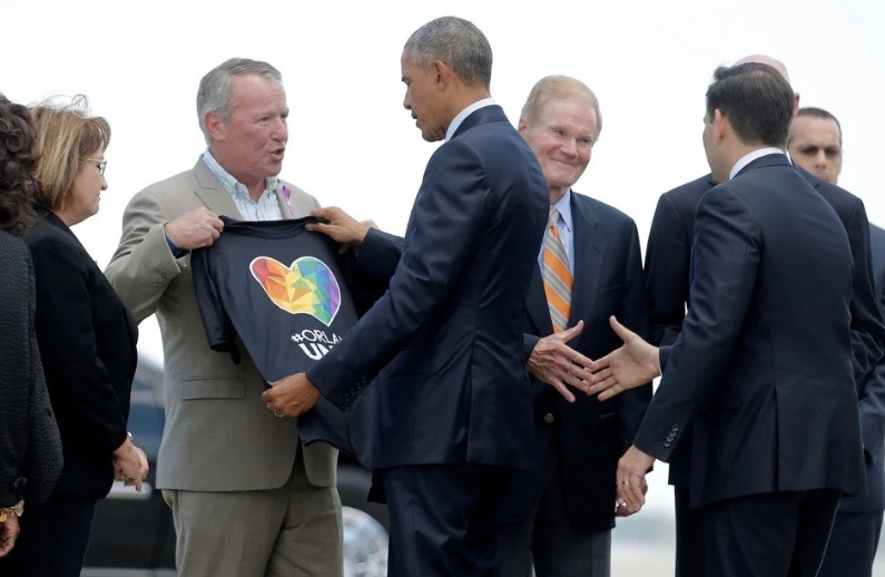 President Obama receives a T-shirt from Mayor Buddy Dyer, second from left, on Thursday. (Carlos Barria/Reuters)