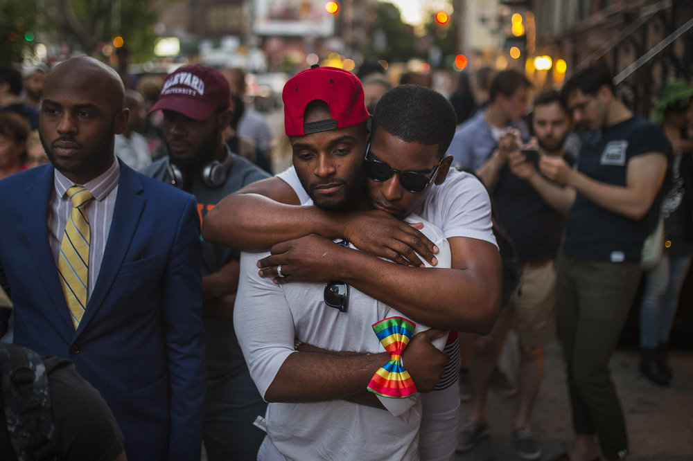 A couple hugs as people gather in front of a makeshift memorial in New York to remember the victims of the mass shooting in Orlando, Fla. on Sunday. Andres Kudacki/AP