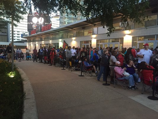 People wait in line for tickets to a memorial service outside the KFC Yum! Center